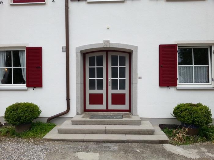 Haustürgestaltung: Professionelle Lackierarbeiten an einer doppelflügeligen Haustür aus Vollholz