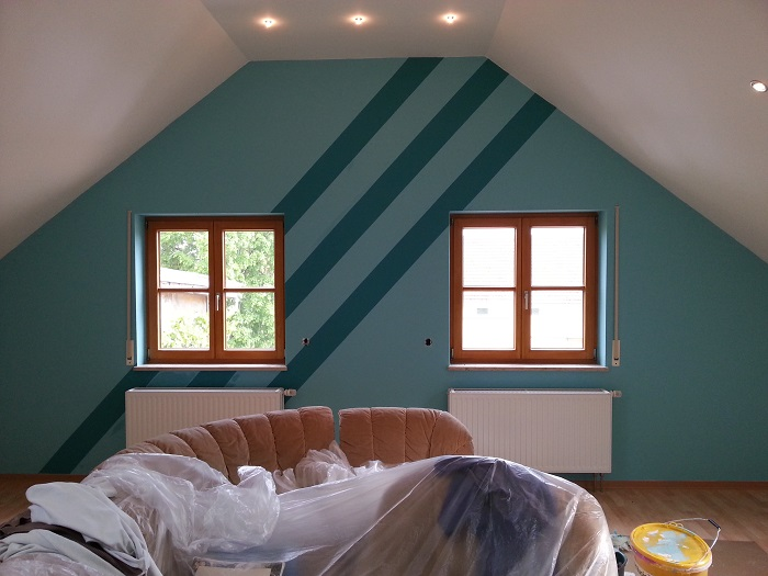 Türkisfarben beschichtete Kinderzimmerwand mit drei dunkelgrün abgesetzten Diagonalstreifen